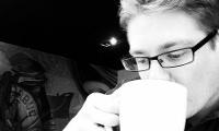 Close-up van een blonde jongeman met bril die en kop koffie drinkt in een cafe